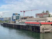 New development along the Vancouver waterfront rises behind the former Red Lion Hotel at the Quay on Wednesday morning. The Washington Legislature has provided $1 million to demolish the landmark building as part of the Port of Vancouver's Terminal 1 redevelopment project.