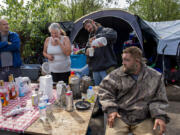David Neff, from left, joins Rae Mackmer, John McKishen and Nathan Berney as they watch the cleanup at the homeless encampment in east Vancouver on Thursday morning. Vancouver is trying to remove garbage from homeless encampments while improving its relationship with its unhoused population.