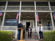 """Gov. Jay Inslee talks to members of the media during a press conference about the """"Take It Outside"""" program to prevent disease transmission. Also pictured are Tracy Fortmann, second from left, superintendent of Fort Vancouver National Historic Site, Stacey Graham, with scarf, interim president of The Historic Trust, Liz Luce of Friends of Fort Vancouver Historic Site and Vancouver Mayor Anne McEnerny-Ogle."""