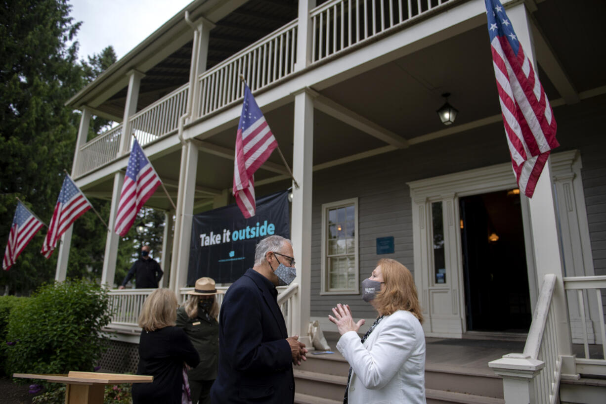 Gov. Jay Inslee talks with Mayor Anne McEnerny-Ogle following a press conference at the Grant House on Friday afternoon.