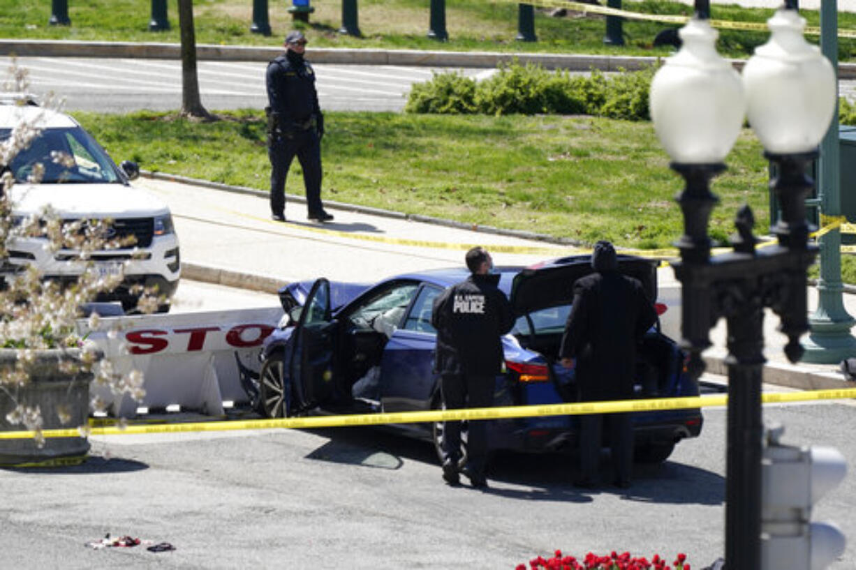 U.S. Capitol Police officers stand near a car that crashed into a barrier on Capitol Hill in Washington, Friday, April 2, 2021. (AP Photo/J.