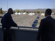 Second Gentleman Douglas Emhoff, right, and Governor Jay Inslee, left, look out over the mass vaccination site at State Fair Park during the coronavirus pandemic Tuesday, April 6, 2021 in Yakima, Wash.