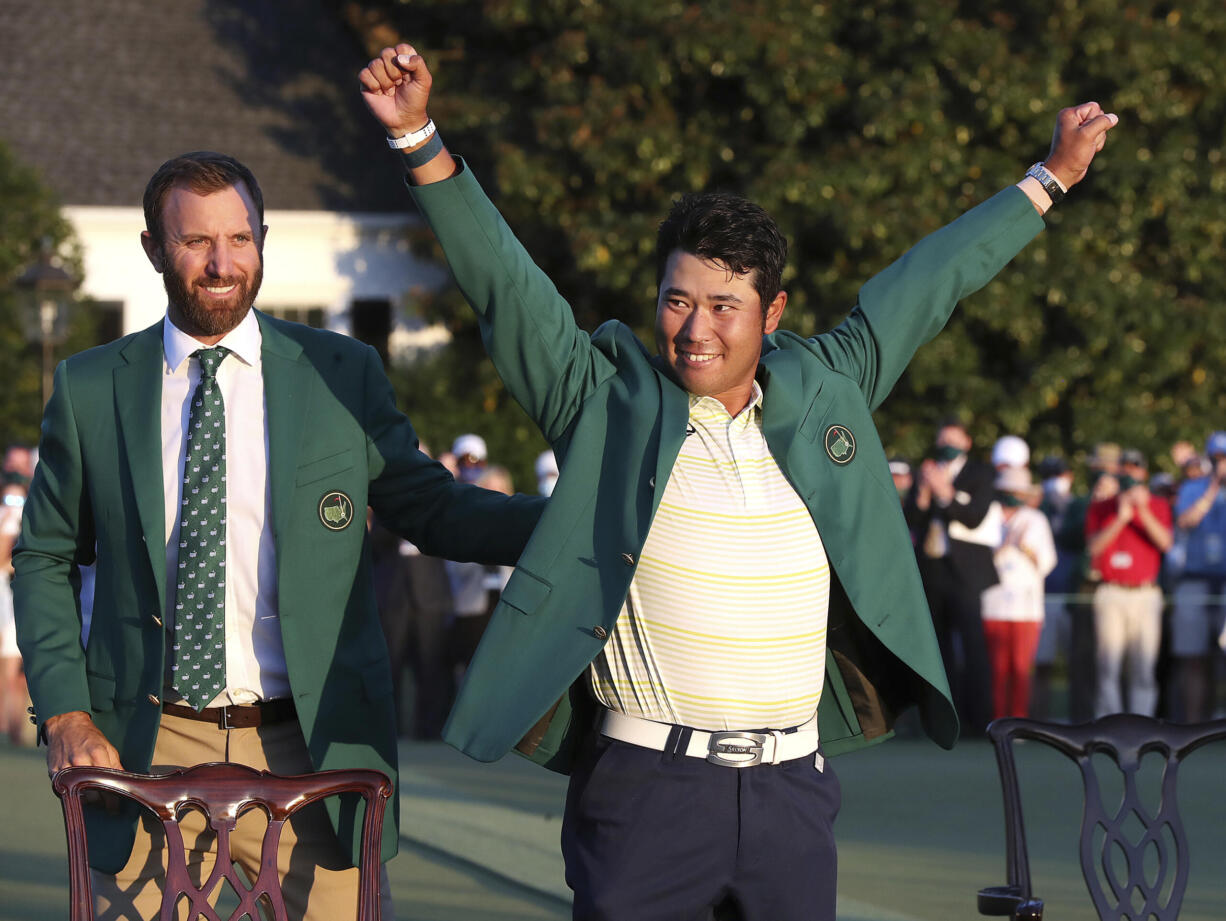 Hideki Matsuyama, of Japan, celebrates while wearing the champion's green jacket as Dustin Johnson looks on after winning the Masters golf tournament on Sunday, April 11, 2021, in Augusta, Ga.