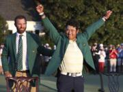Hideki Matsuyama, of Japan, celebrates while wearing the champion's green jacket as Dustin Johnson looks on after winning the Masters golf tournament on Sunday, April 11, 2021, in Augusta, Ga.