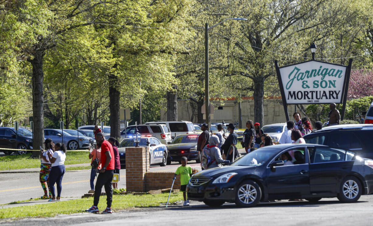 People gather outside Austin-East Magnet High School in Knoxville, Tenn., following a shooting at the school Monday, April 12, 2021.