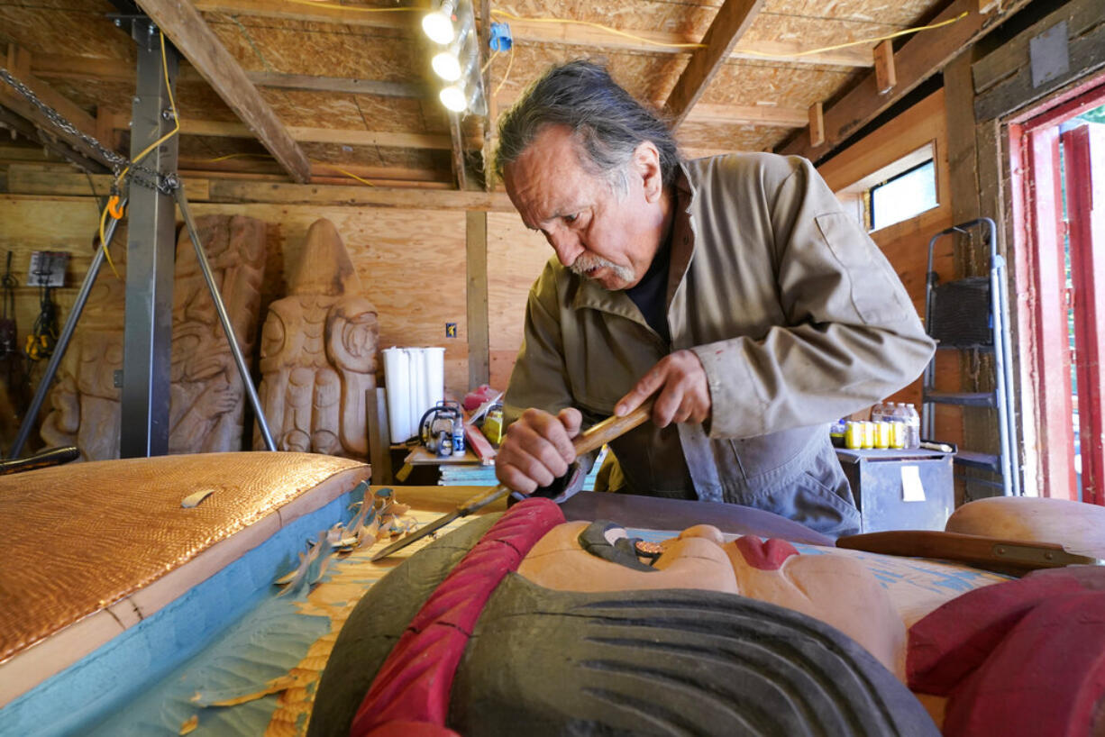 Lummi Nation lead carver Jewell James works on the final details of a nearly 25-foot totem pole to be gifted to the Biden administration, Monday, April 12, 2021, on the Lummi Reservation, near Bellingham, Wash. The pole, carved from a 400-year old red cedar, will make a journey from the reservation past sacred indigenous sites, before arriving in Washington, D.C. in early June. Organizers said that the totem pole is a reminder to leaders to honor the rights of Indigenous people and their sacred sites.