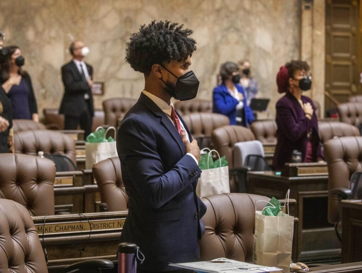 FILE - In this Jan. 11, 2021, file photo, Rep. Jesse Johnson, D-Federal Way, stands with other members at the beginning of the House session, where legislators were spaced at a social distance, in Olympia, Wash. Johnson hopes to see the Legislature end qualified immunity for police officers, which would allow them to be sued in state court, and to see it authorize community oversight boards that could have input on local policies and receive complaints about officers.