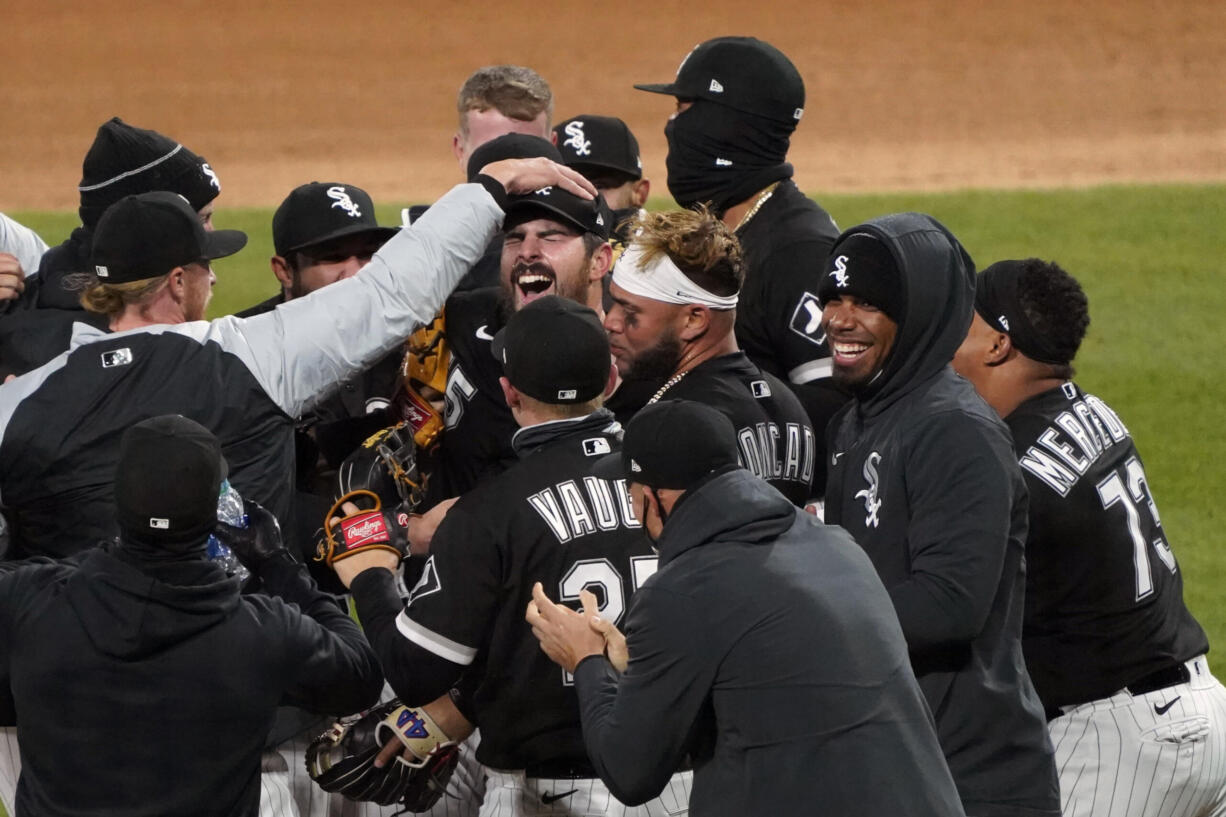 Chicago White Sox starting pitcher Carlos Rodon, center, celebrates his no hitter against the Cleveland Indians with his teammates in a baseball game, Wednesday, April, 14, 2021, in Chicago.