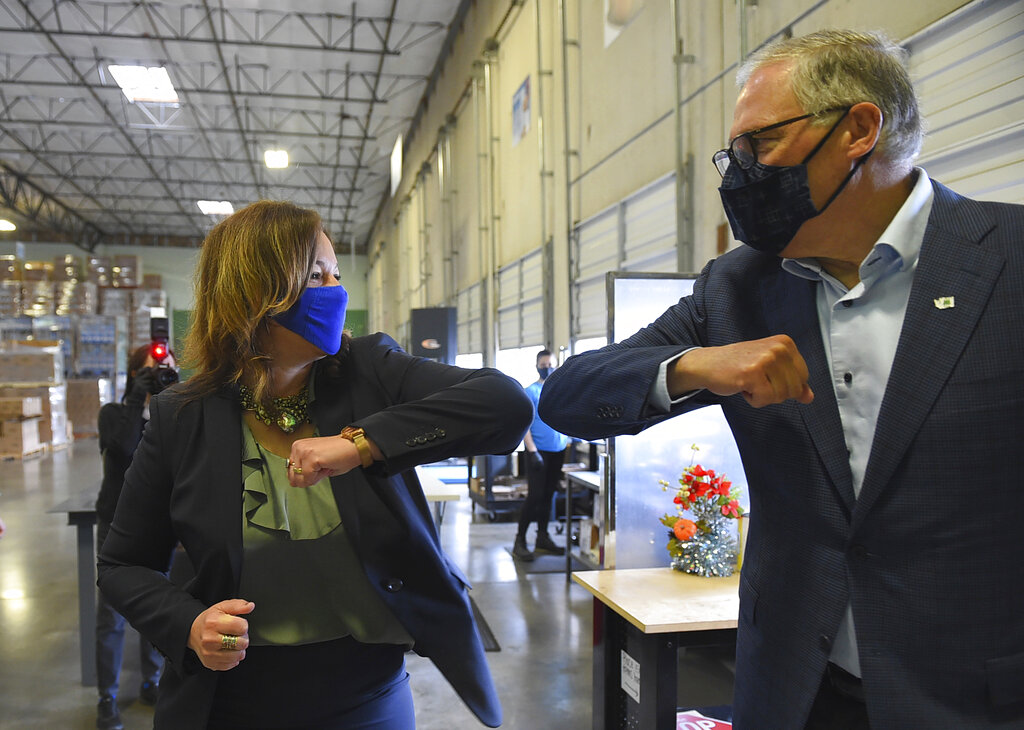 Washington Gov. Jay Inslee and ECOS President and CEO Kelly Vlahakis-Hanks bump elbows as the greet one another before a tour of ECOS manufacturing facility and chemistry lab, Thursday, April 22, 2021, during Earth Day in Lacey, Wash. The company manufactures environmentally safe cleaning and household products and is rated carbon neutral, diverting over 95% of their waste from landfills.