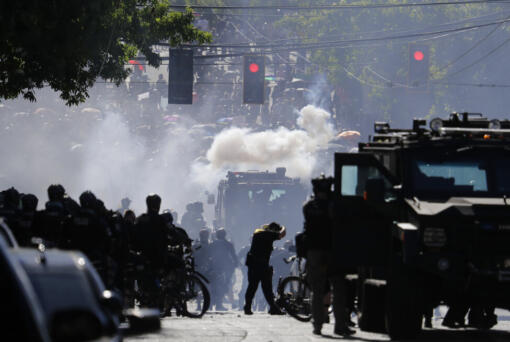 FILE - In this July 25, 2020, file photo, smoke rises as police clash with protester during a Black Lives Matter protest near the Seattle Police East Precinct headquarters in Seattle. Mayors, county executives or even the governor would have to give their approval before police could use tear gas to quell riots under a compromise reached in the Washington Legislature. A conference committee of the House and Senate met Thursday, April 22, 2021, to reconcile versions of a police tactics bill already approved by each chamber. (AP Photo/Ted S.