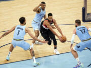 Portland Trail Blazers' CJ McCollum, center, drives between Memphis Grizzlies' defenders Kyle Anderson (1), De'Anthony Melton (0) and Jonas Valanciunas (17) in the second half of an NBA basketball game Wednesday, April 28, 2021, in Memphis, Tenn.