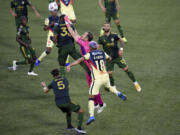 Portland Timbers goalkeeper Jeff Attinella, center, punches the ball away as Larrys Mabiala, left, and América defender Bruno Valdez, right, close in during the first half of a CONCACAF Champions League soccer match in Portland, Ore., Wednesday, April 28, 2021.