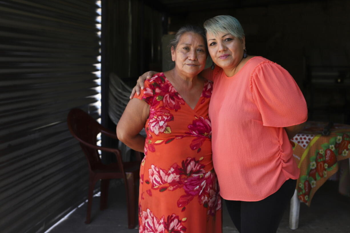 Iris Franco, right, hugs her mother, Elsa Victorina Franco, at her home, in El Ranchador, Santa Ana, El Salvador, Friday, March 5, 2021. The Salvadoran family lives humbly but is in a better place thanks to financial support from a family member in the United States who is part of the Temporary Protected Status program.