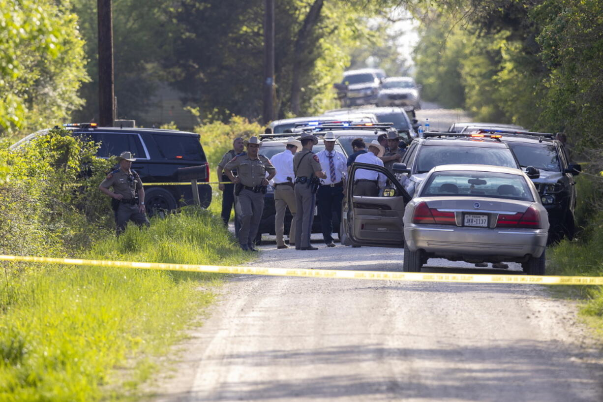 First responders work at the scene of the apprehension of a suspect at a residence in Bedias, Texas, Thursday, April 8, 2021, following a shooting at Kent Moore Cabinets in Bryan, Texas. One person was killed and several people were wounded Thursday in the wake of a shooting at the cabinet-making business in Bryan, authorities said, and a state trooper was later shot during a manhunt that resulted in the suspected shooter being taken into custody.