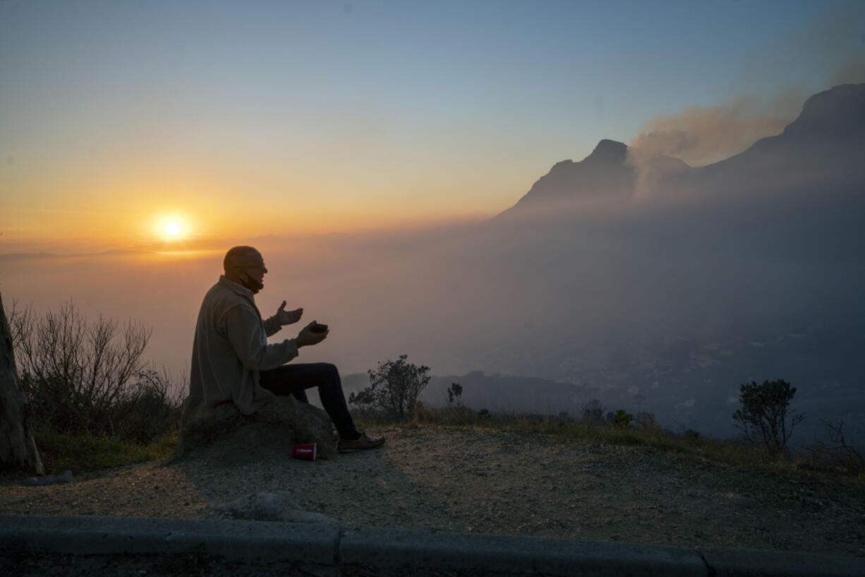 A Capetonian watches the sun rise from the top of Signal Hill as smoke engulfs the city of Cape Town, South Africa, Tuesday April 20, 2021. A massive fire spreading on the slopes of the city's famed Table Mountain, at right, is kept under control as firemen and helicopters take advantage of the low winds to contain the blaze.