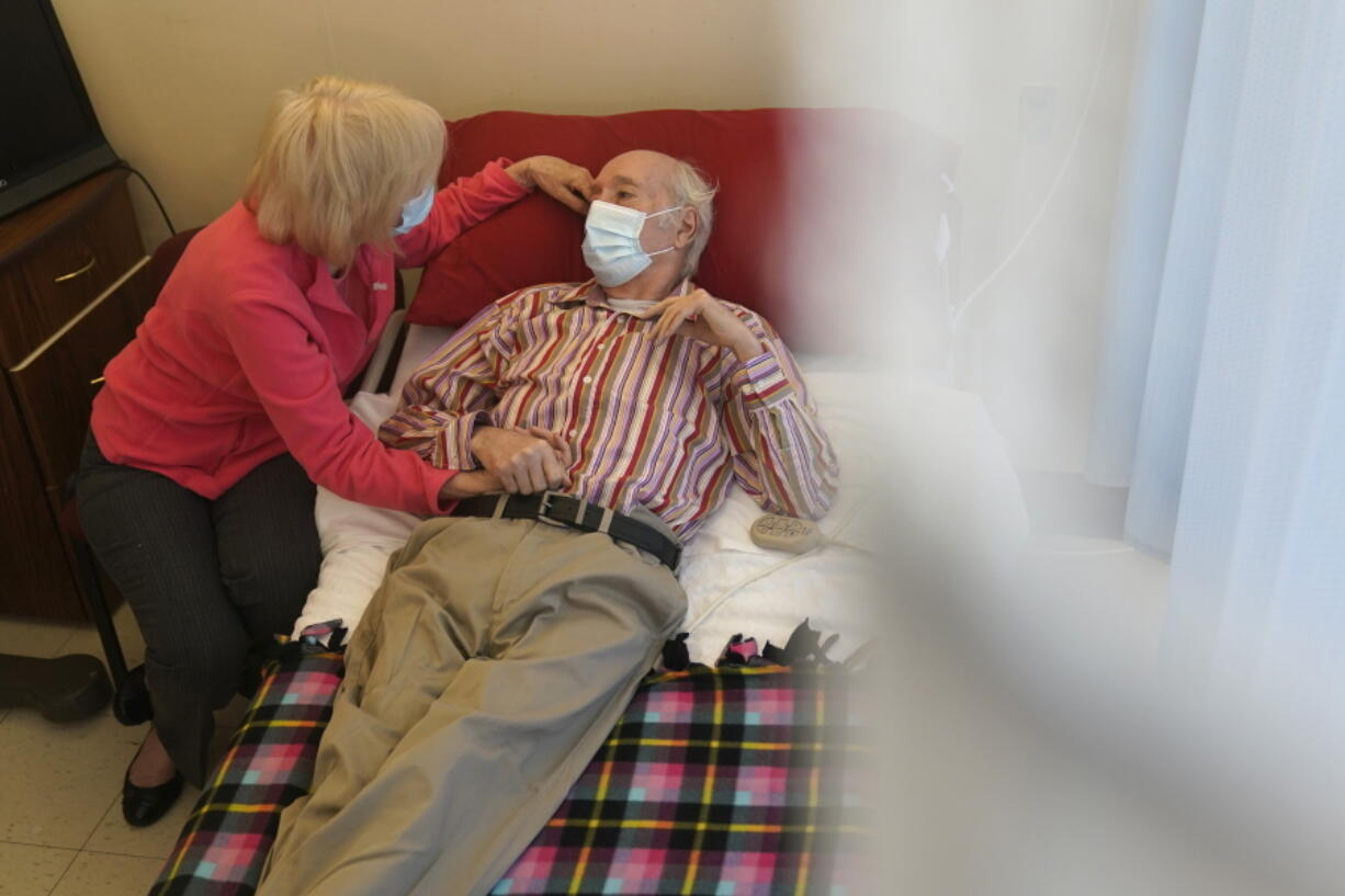 Patricia Sain visits with her husband Clyde Sain, who is in long term care, at Bergen New Bridge Medical Center in Paramus, N.J., Thursday, April 8, 2021. This was the first visit since early March 2020 that Patricia has been able to touch her husband and visit with him indoors.