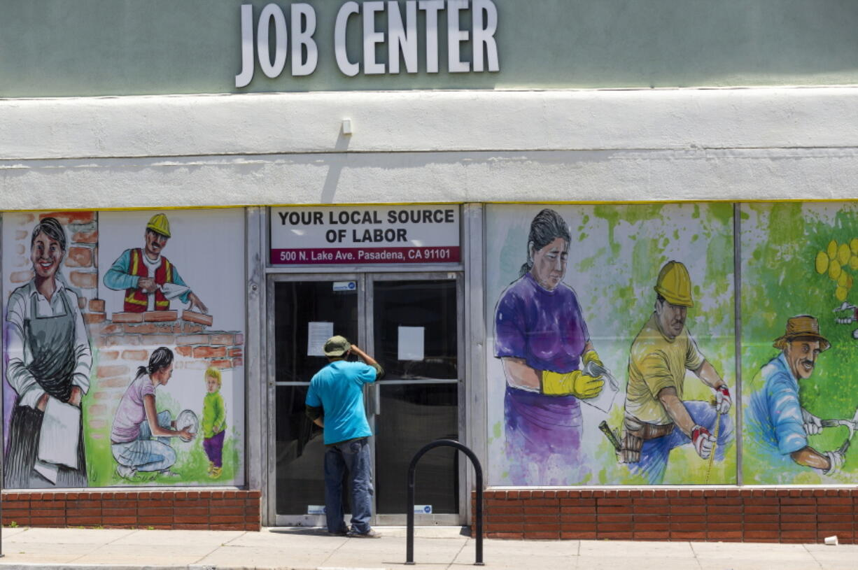 FILE - In this May 7, 2020, file photo, a person looks inside the closed doors of the Pasadena Community Job Center in Pasadena, Calif., during the coronavirus outbreak. While most Americans have weathered the pandemic financially, about 38 million say they are worse off now than before the outbreak began in the U.S. According to a new poll from Impact Genome and The Associated Press-NORC Center for Public Affairs Research 55% of Americans say their financial circumstances are about the same now as a year ago, and 30% say their finances have improved.