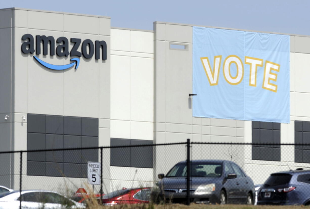 FILE - In this March 30, 2021 file photo, a banner encouraging workers to vote in labor balloting is shown at an Amazon warehouse in Bessemer, Ala.  The retail union that failed to unionize Amazon workers at the Alabama warehouse wants the results to be thrown out, saying that the company illegally interfered with the voting process.The Retail, Wholesale and Department Store Union said in a filing that Amazon threatened workers with layoffs and even the closing of the warehouse if they unionized.