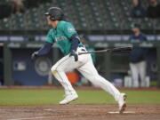 Seattle Mariners' Dylan Moore watches his RBI single during the third inning of the team's baseball game against the Los Angeles Angels, Friday, April 30, 2021, in Seattle. (AP Photo/Ted S.