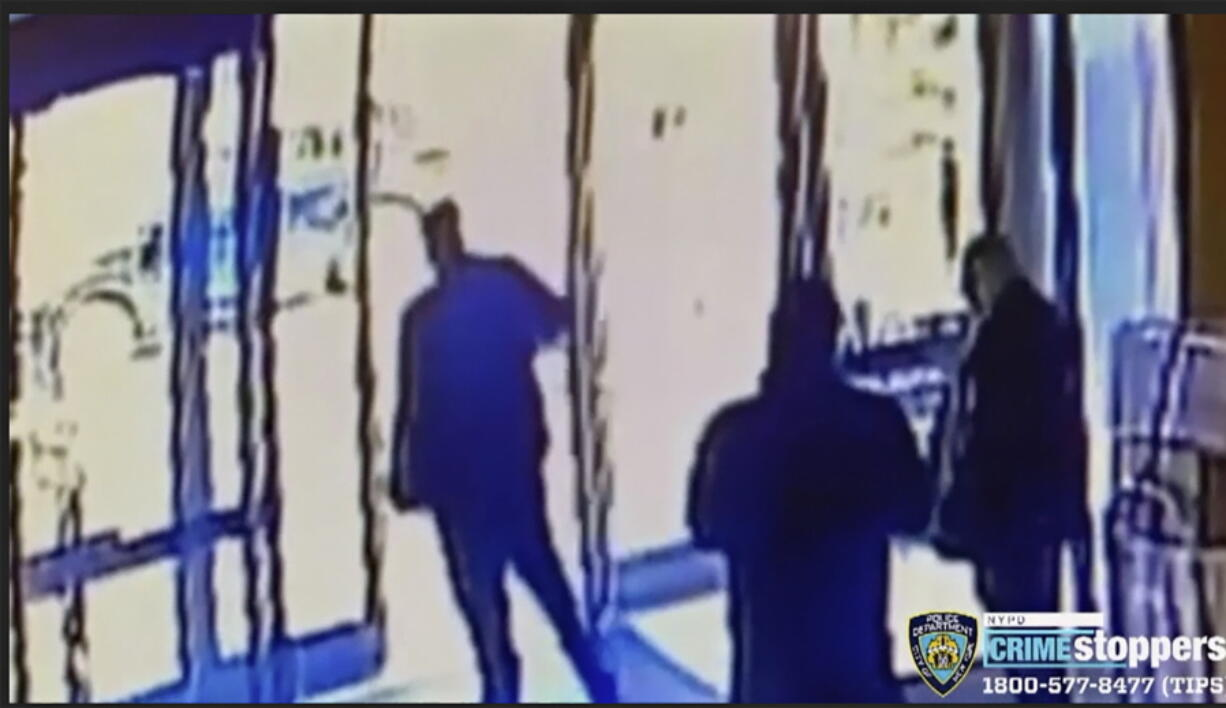 This image taken from surveillance video provided by the New York City Police Department shows an apartment building employee, center, closing the building's front door after a man assaulted a 65-year-old Asian American woman, Monday afternoon, March 29, 2021, a few blocks from New York's Times Square.
