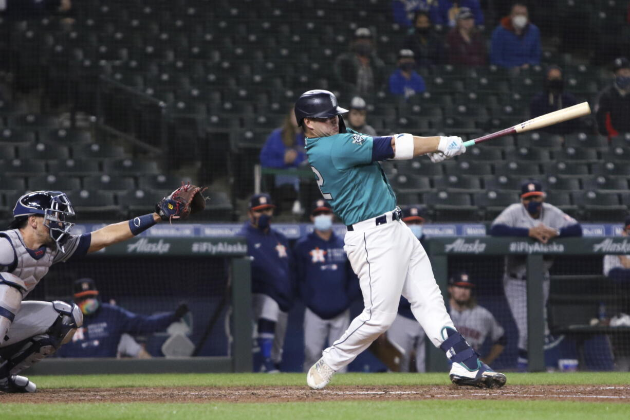 Seattle Mariners' Ty France follows through on a single that drove in the winning run, next to Houston Astros catcher Jason Castro during the ninth inning of a baseball game Friday, April 16, 2021, in Seattle. The Mariners won 6-5.