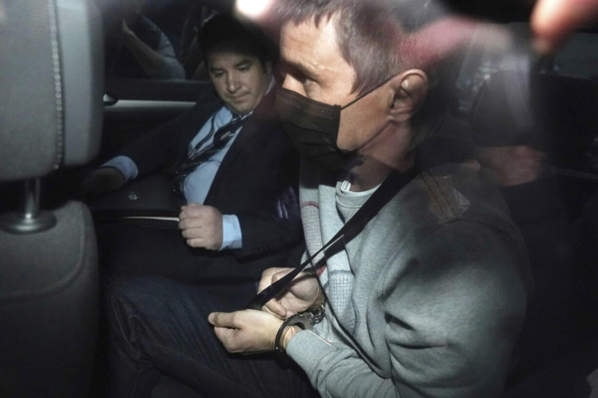 """Richard Pusey, right, is taken away from his home property by police in Melbourne, Australia on April 23, 2020. Pusey was sentenced to 10 months in prison on Wednesday, April 28, 2021, for offenses including what a judge described as the """"heartless, cruel and disgraceful"""" filming of four dead and dying police officers who had just been hit by a truck on an Australian freeway."""