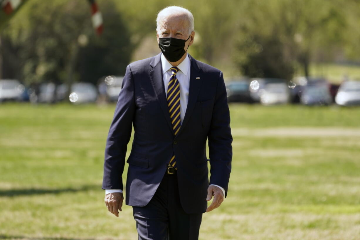 President Joe Biden walks over to speak to members of the media after arriving on the Ellipse on the National Mall after spending the weekend at Camp David, Monday, April 5, 2021, in Washington.