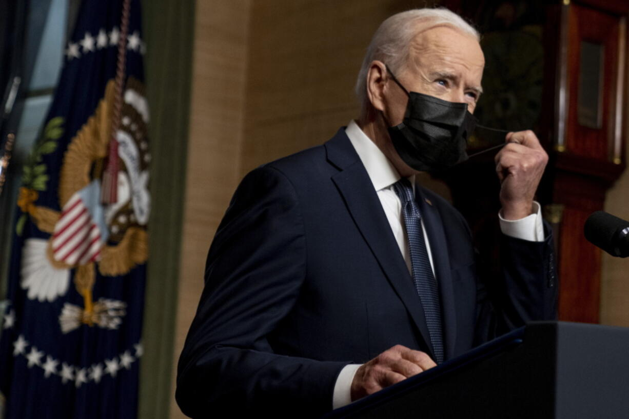 FILE - In this Wednesday, April 14, 2021, file photo, President Joe Biden removes his mask to speak at a news conference at the White House, in Washington. Ten liberal senators are urging Biden to back India and South Africa's appeal to the World Trade Organization to temporarily relax intellectual property rules so coronavirus vaccines can be manufactured by nations that are struggling to inoculate their population.