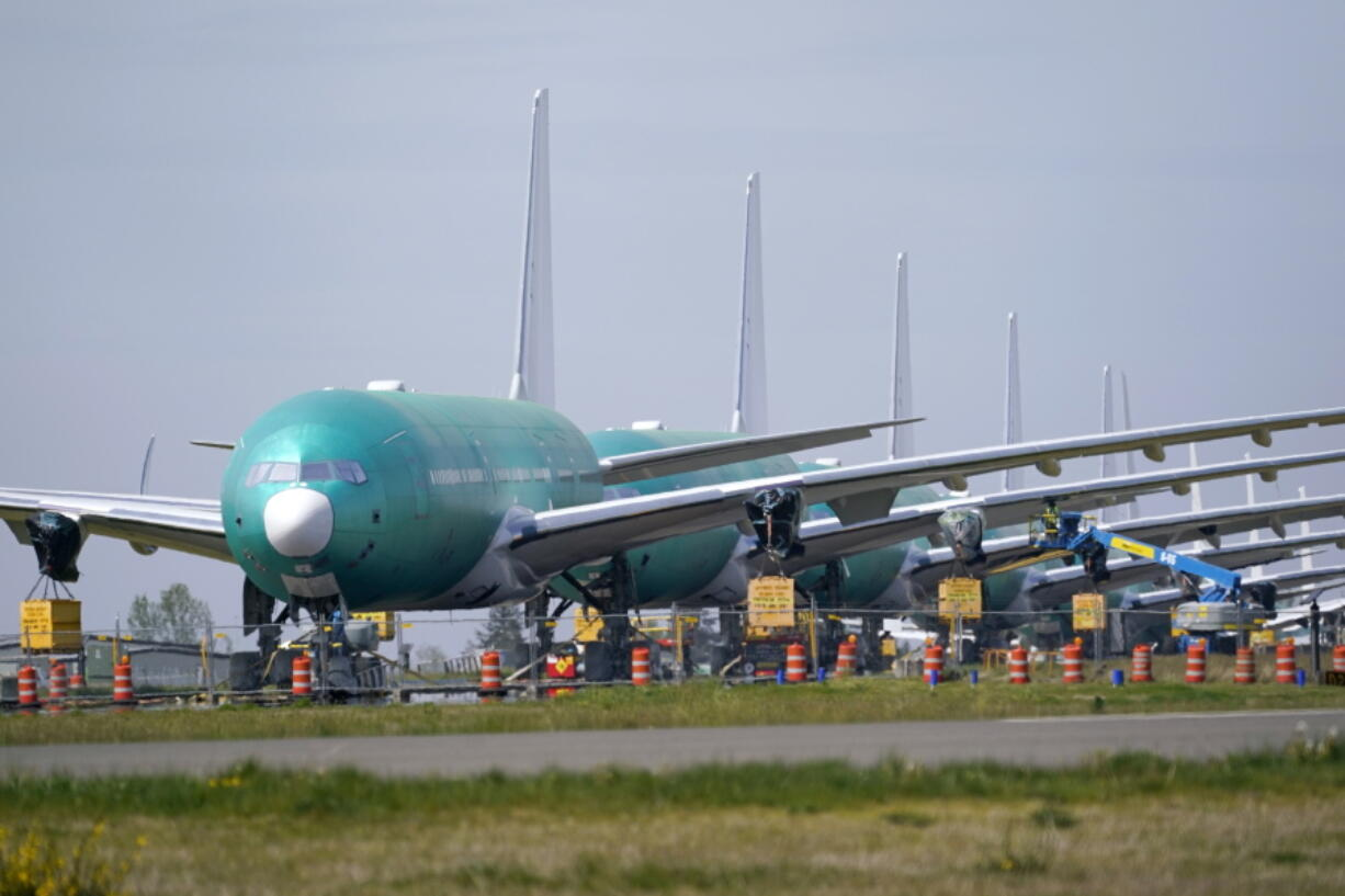 A line of Boeing 777X jets are parked nose to tail on an unused runway at Paine Field, near Boeing's massive production facility, Friday, April 23, 2021, in Everett, Wash.  Boeing Co. on Wednesday, April 28,  reported a loss of $537 million in its first quarter. The Chicago-based company said it had a loss of 92 cents per share. Losses, adjusted for non-recurring gains, were $1.53 per share.