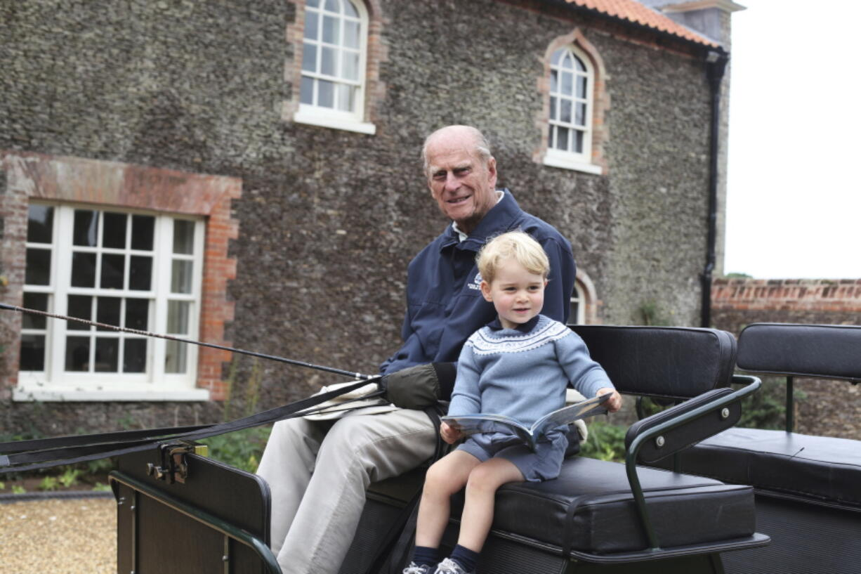 In this undated handout photo provided by the Duke and Duchess of Cambridge, Britain's Prince Philip sits with his great-grandson Prince George in England. Prince Philip, the irascible and tough-minded husband of Queen Elizabeth II who spent more than seven decades supporting his wife in a role that mostly defined his life, died on Friday, April 9, 2021.