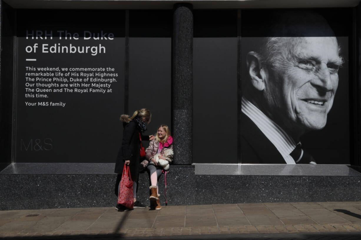 Isabella Disley greets her mother Tara Lynn and her dog Coco next to a portrait of Prince Philip, which adorns a window of a department store in Windsor, England, Friday, April 16, 2021. Prince Philip husband of Britain's Queen Elizabeth II died April 9, aged 99, his funeral will take place Saturday at Windsor Castle in St George's Chapel.