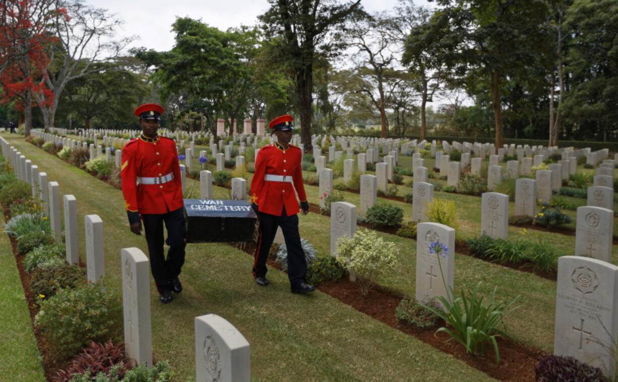 "FILE - In this Sunday, Nov. 13, 2016 file photo, two members of Kenya's Military Police walk past graves as they leave after attending a Remembrance Sunday event, to honor the contribution of those British and Commonwealth military who died in the two World Wars and later conflicts, at the Nairobi War Cemetery in Kenya. The Commonwealth War Graves Commission has apologized after an investigation found that at least 161,000 mostly Africans and Indians who died fighting for the British Empire during World War I weren't properly honored due to ""pervasive racism"", according to findings released Thursday, April 22, 2021."