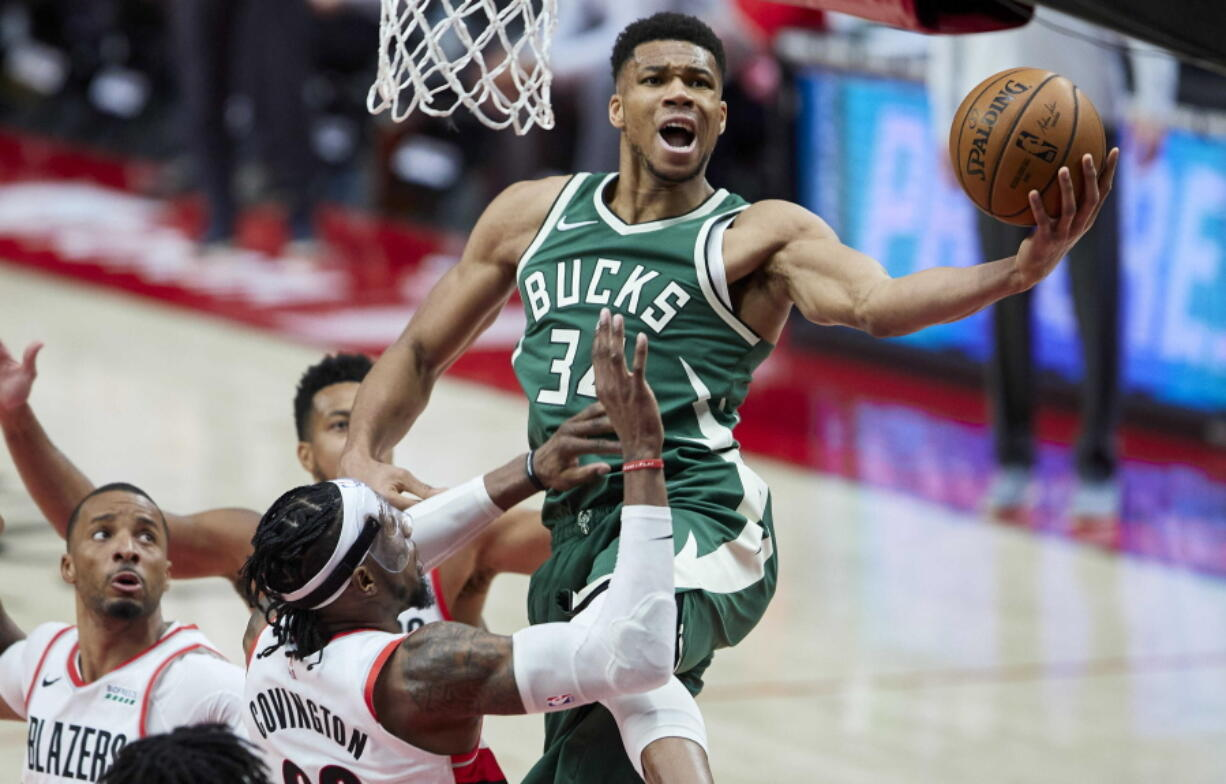 Milwaukee forward Giannis Antetokounmpo, right, drives to the basket against the Portland Trail Blazers on Friday.