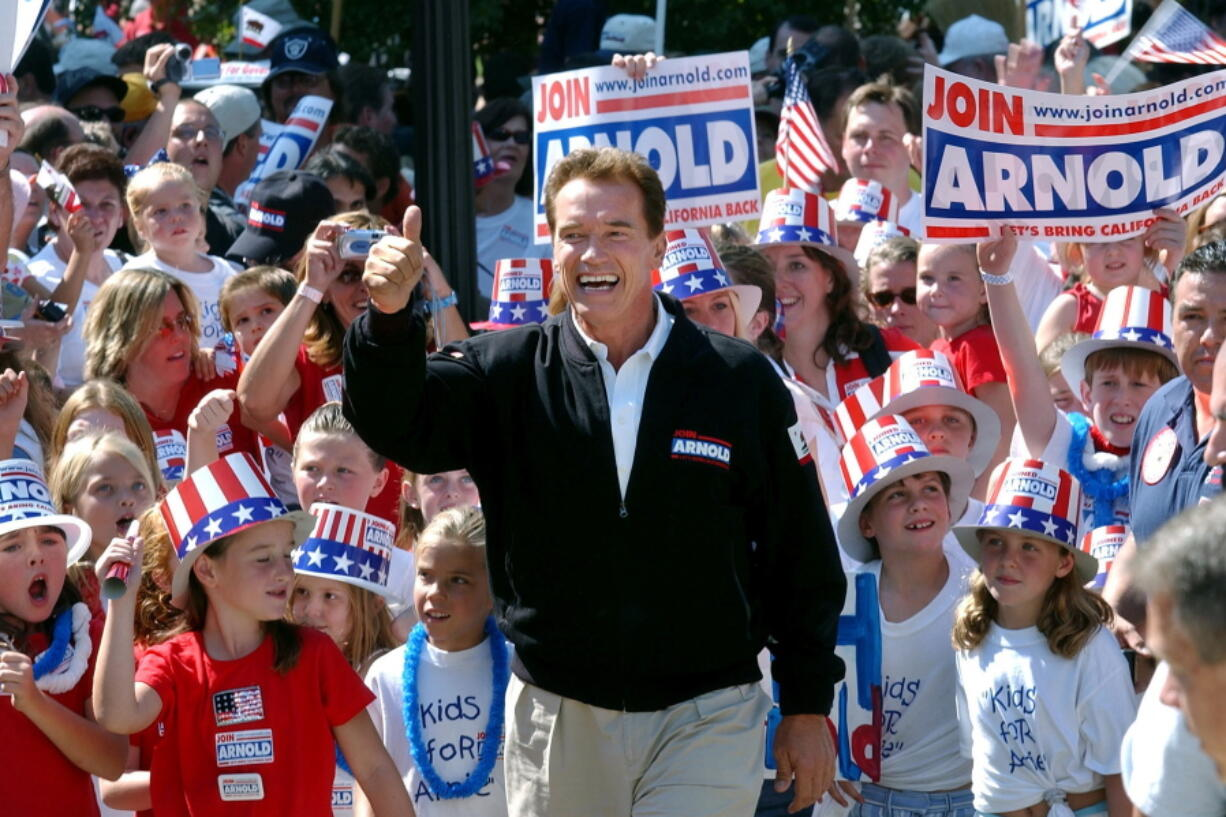 FILE - In this Oct. 5, 2003, file photo, then-Republican candidate for California governor Arnold Schwarzenegger walks up the steps to the state Capitol surrounded by children and waving to supporters during a campaign rally in Sacramento, Calif. No candidate of Schwarzenegger's fame has yet emerged in the expected 2021 recall election against Democratic Gov. Gavin Newsom.