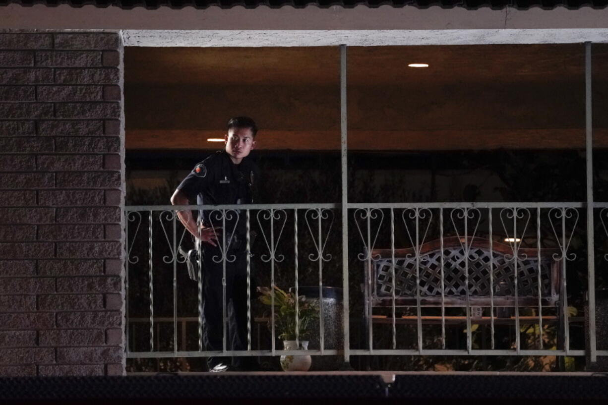 A police officer surveys the scene after a shooting at an office building in Orange, Calif., Wednesday, March 31, 2021. The shooting killed several people, including a child, and injured another person before police shot and wounded the suspect, police said. (AP Photo/Jae C.