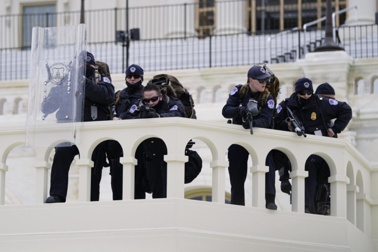 FILE - In this Jan. 6, 2021, file photo, police keep a watch on demonstrators who tried to break through a police barrier at the Capitol in Washington. A blistering internal report by the U.S. Capitol Police describes a multitude of missteps that left the force unprepared for the Jan. 6 insurrection - riot shields that shattered upon impact, expired weapons that couldn't be used, inadequate training and an intelligence division that had few set standards.