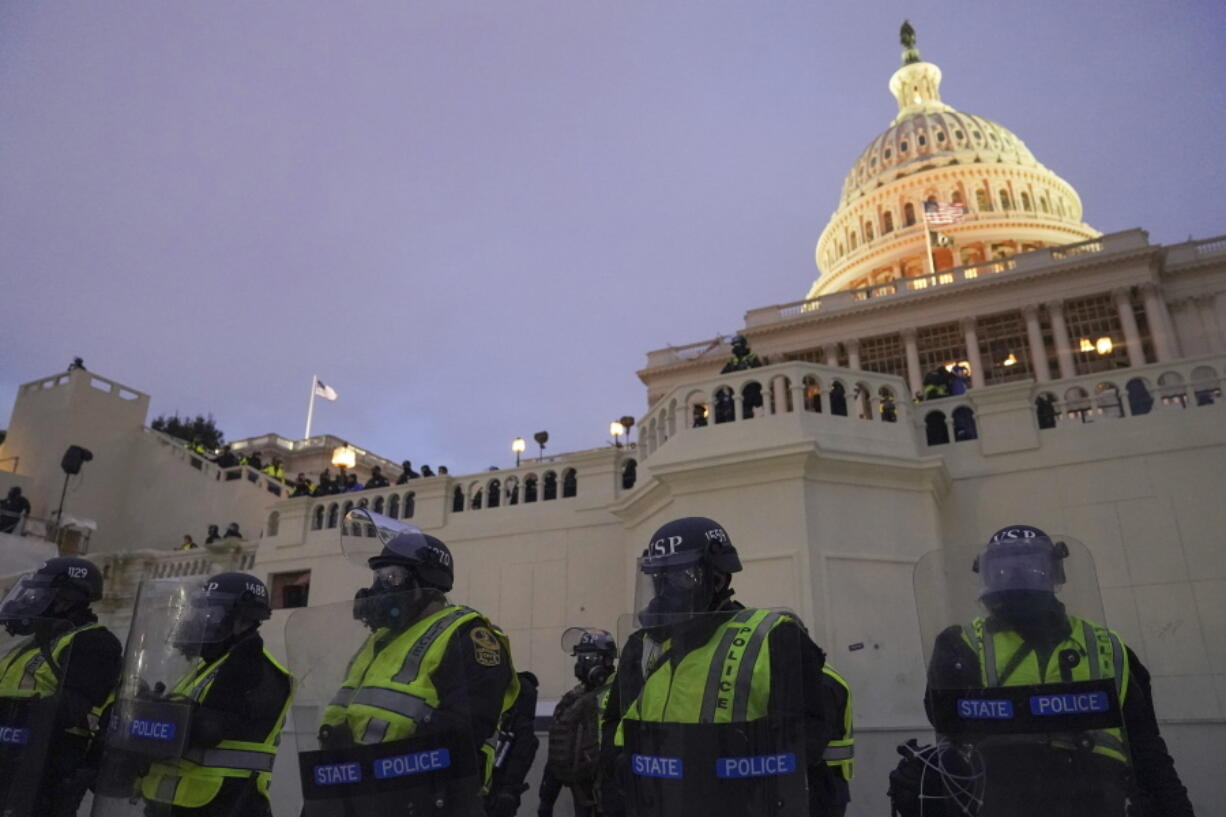 In this Wednesday, Jan. 6, 2021, photo, police form a line to guard the Capitol after violent rioters stormed the Capitol, in Washington. The top watchdog for the U.S. Capitol Police will testify to Congress for the first time about the department's broad failures before and during the Jan. 6 insurrection. Among them was missed intelligence and old weapons that officers didn't feel comfortable using.