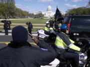 With the U.S. Capitol in the background, U.S. Capitol Police officers salute as procession carries the remains of a U.S. Capitol Police officer who was killed after a man rammed a car into two officers at a barricade outside the Capitol in Washington, Friday, April 2, 2021.