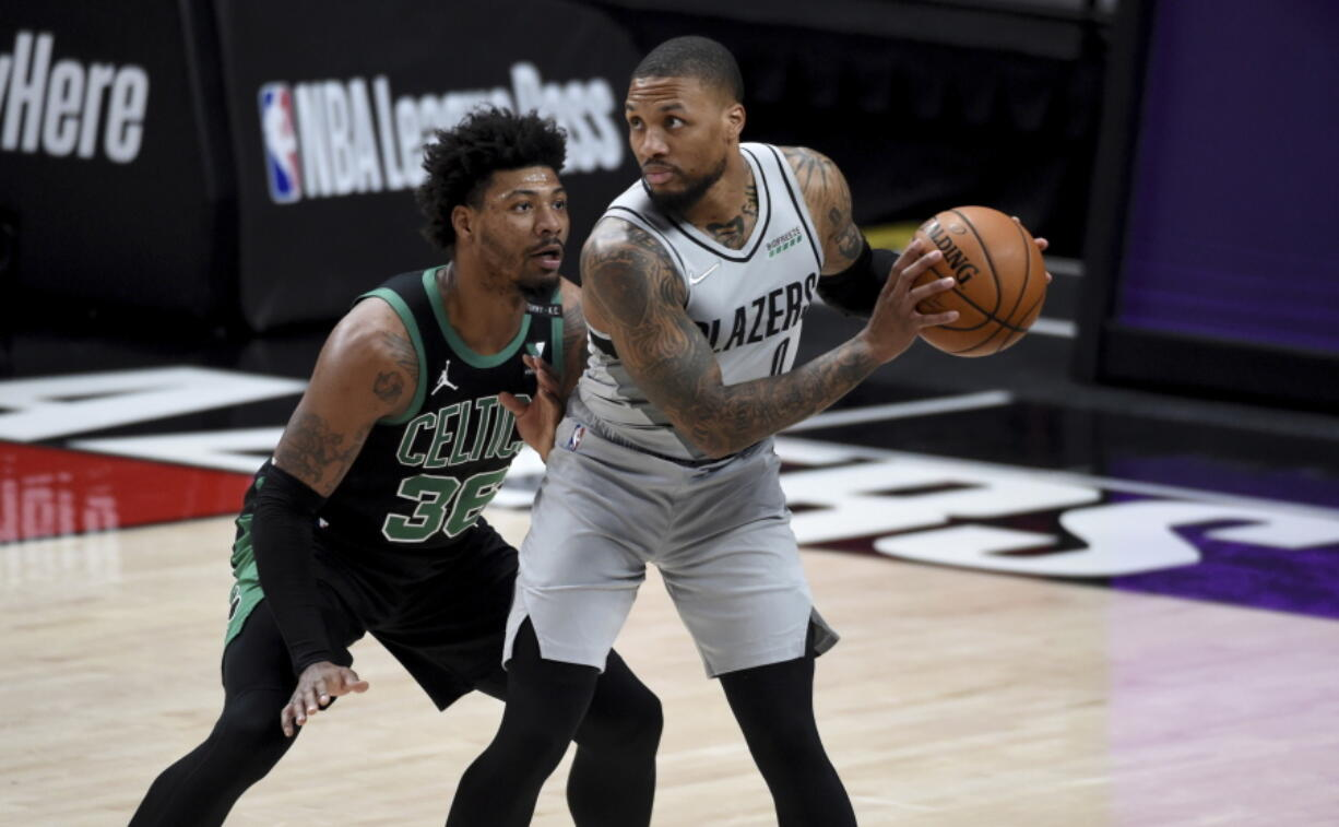Portland Trail Blazers guard Damian Lillard, right, looks to drive the ball on Boston Celtics guard Marcus Smart, left, during the first half of an NBA basketball game in Portland, Ore., Tuesday, April 13, 2021.