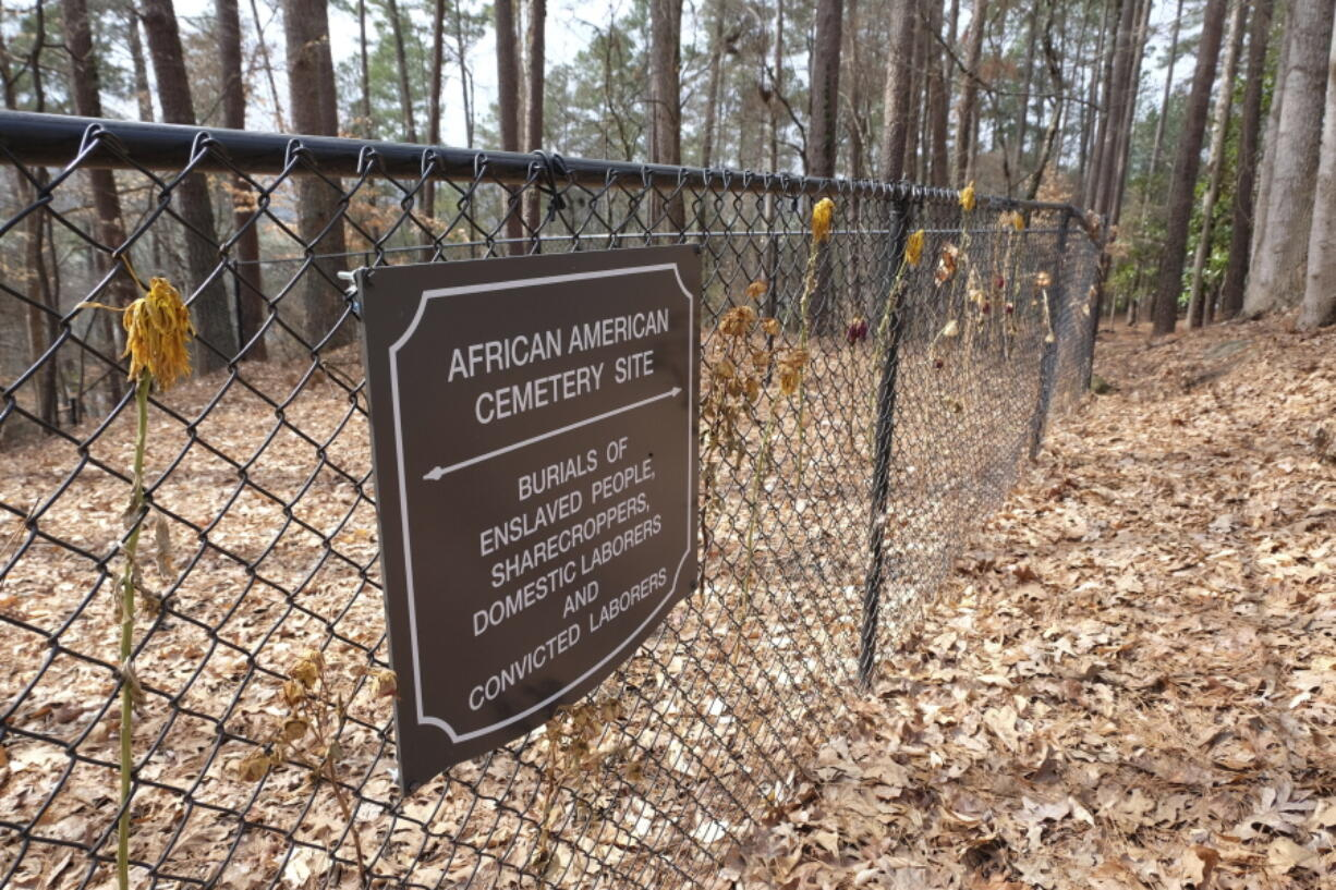 Flowers adorn a fence marking an African American cemetery site at Woodland Cemetery in Clemson, South Carolina on Sunday, Feb.  28, 2021.   Students at Clemson University who found an unkempt graveyard on campus last year sparked the discovery of more than 600 unmarked graves most likely belonging to enslaved Black people, sharecroppers and convicted laborers. The revelation has Clemson working to identify the dead and properly honor them amid a national reckoning by universities about their legacies of racial injustice.