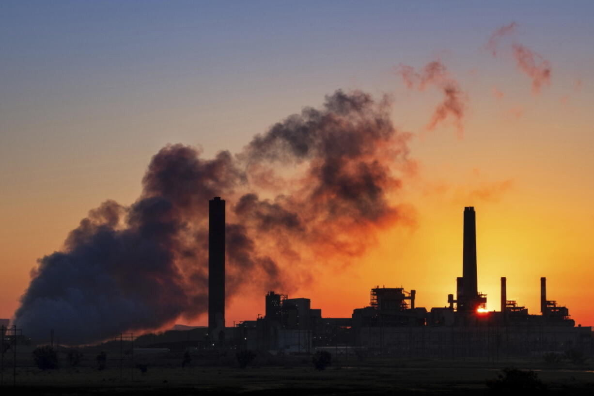 The Dave Johnson coal-fired power plant is silhouetted July 27, 2018, against the morning sun in Glenrock, Wyo.