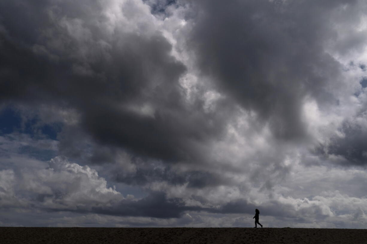 A woman strolls along the beach under rain clouds March 10 in Seal Beach, Calif. Rainstorms grew more erratic across most of the West over the past 50 years. (jae c.