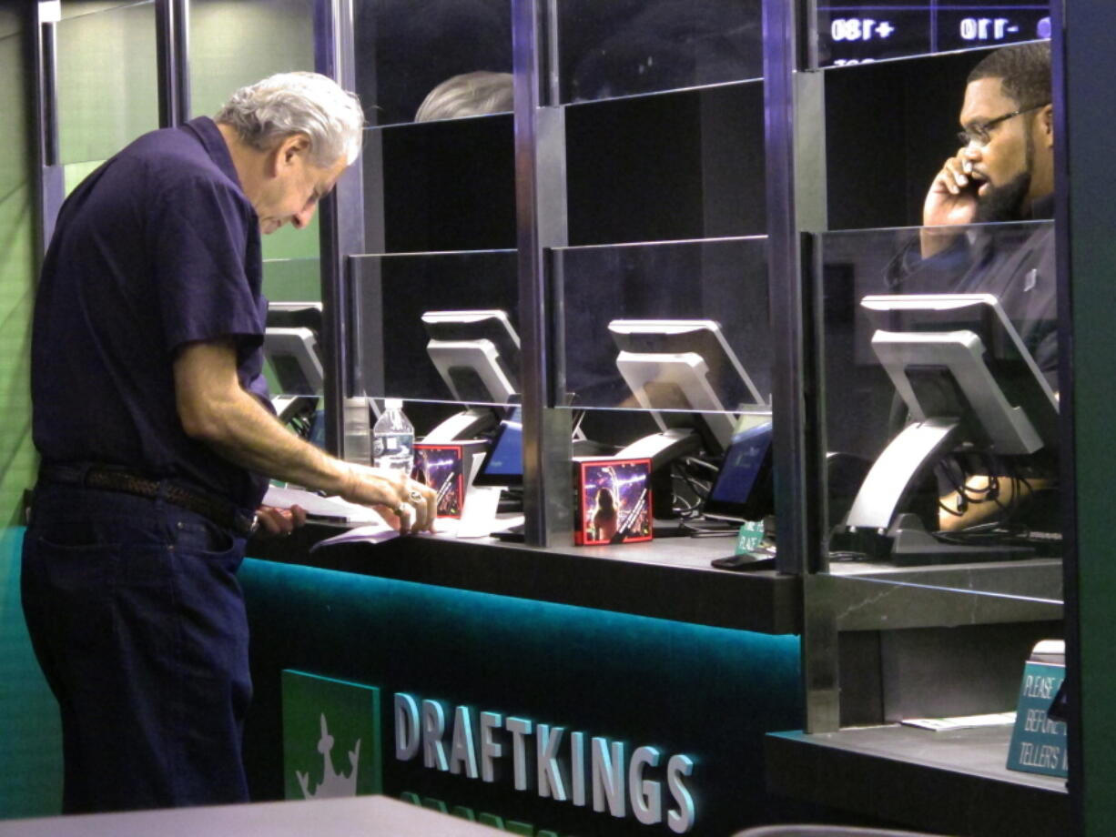 A customer makes a sports bet at the DraftKings sports book at Resorts Casino in Atlantic City, N.J. On Tuesday, March 30, 2021, DraftKings acquired the video production and distribution company Vegas Sports Information Network to add content to DraftKings' operations in 14 states.