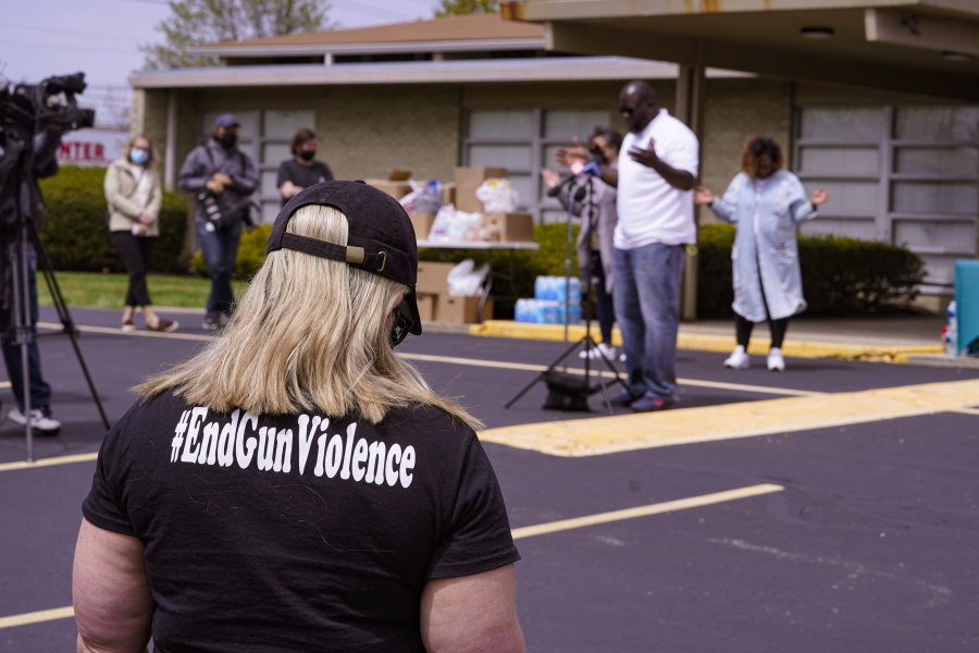 A women wears a shirt calling for the end of gun violence during a vigil at the Olivet Missionary Baptist Church for the victims of the shooting at a FedEx facility in Indianapolis, Saturday, April 17, 2021. A gunman killed eight people and wounded several others before taking his own life in a late-night attack at a FedEx facility near the Indianapolis airport, police said.