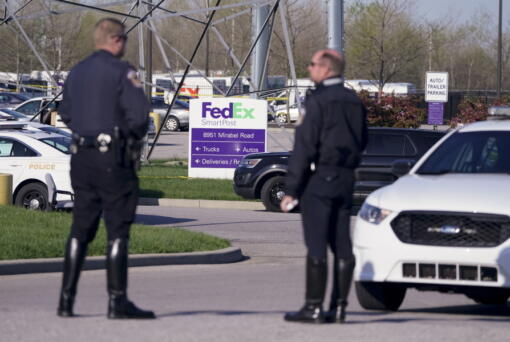 Authorities confer at the scene where multiple people were shot at the FedEx Ground facility early Friday morning, April 16, 2021, in Indianapolis. A gunman killed eight people and wounded several others before apparently taking his own life in a late-night attack at a FedEx facility near the Indianapolis airport, police said, in the latest in a spate of mass shootings in the United States after a relative lull during the pandemic.
