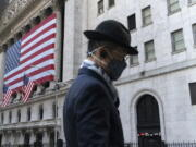FILE - In this Nov. 16, 2020 file photo a man wearing a mask passes the New York Stock Exchange in New York. Stocks are wavering in early trading on Wall Street, holding the market near record highs it set earlier in the week. The S&P 500 edged up 0.1% early Wednesday, April 7, 2021, and the Dow Jones Industrial Average climbed 0.2%.