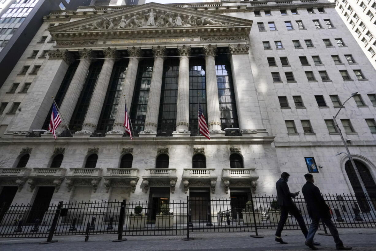 FILE - In this March 23, 2021 file photo, pedestrians walk past the New York Stock Exchange in New York's Financial District.  Stocks are opening modestly lower on Wall Street, Thursday, April 22,  led by drops in banks and technology companies.