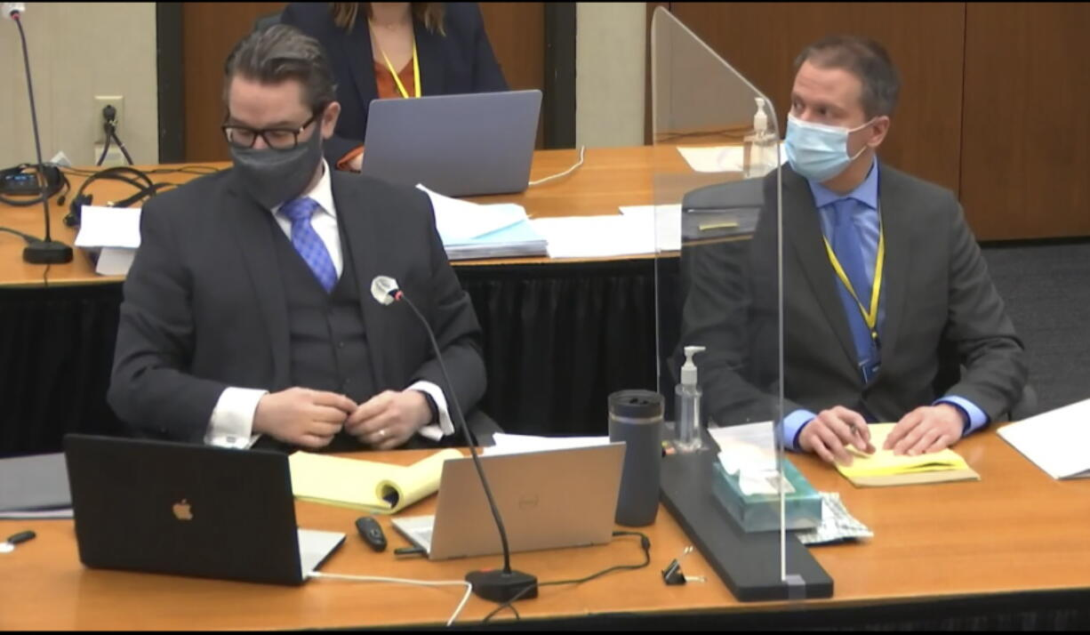 In this image from video, defense attorney Eric Nelson, left, and defendant, former Minneapolis police officer Derek Chauvin, right, listen, Wednesday, April 14, 2021, as Hennepin County Judge Peter Cahill presides over motions in the trial of Chauvin at the Hennepin County Courthouse in Minneapolis. Chauvin is charged in the May 25, 2020 death of George Floyd.