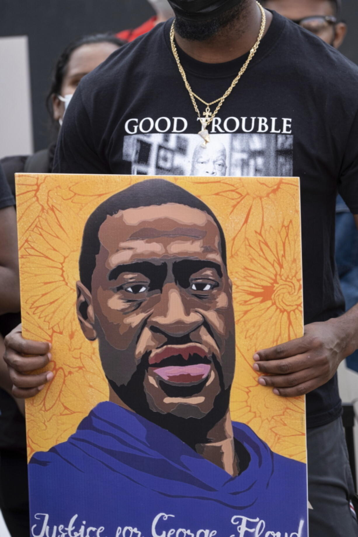 A person holds a poster of George Floyd on Tuesday in Atlanta.