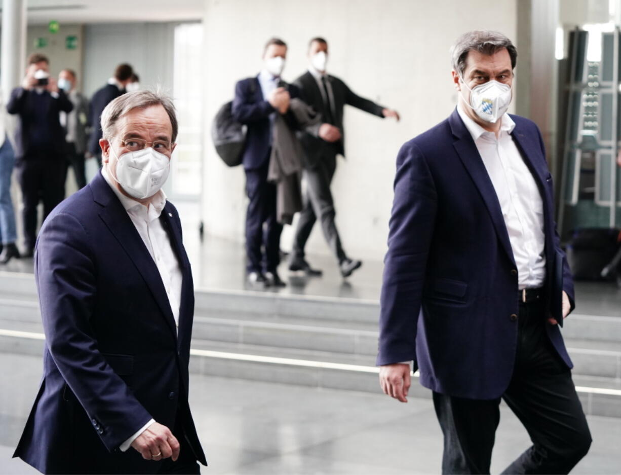 The chairman of the German Christian Democratic Party (CDU), ArminLaschet, left, and the chairman of the German Christian Social Union (CSU), Markus Soeder, right, arrive for a statement folowing a closed meeting of the federal palrliament factions of both partys in Berlin, Germany, Sunday, April 11, 2021. The two party chairmen and German state governors want to become the center-right candidate for the country's Sept. 26 national election, the German news agency dpa reported Sunday.